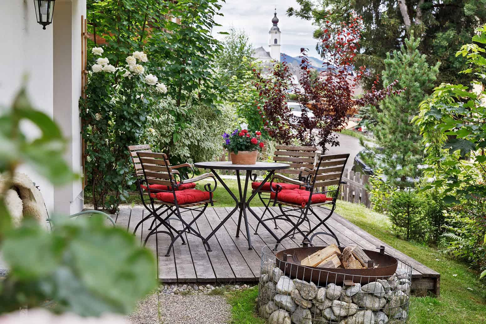 Man sieht einen kleinen runden Tisch mit vier Stühlen auf einer Veranda. Diese ist von Blumen und Bäumen umgeben.