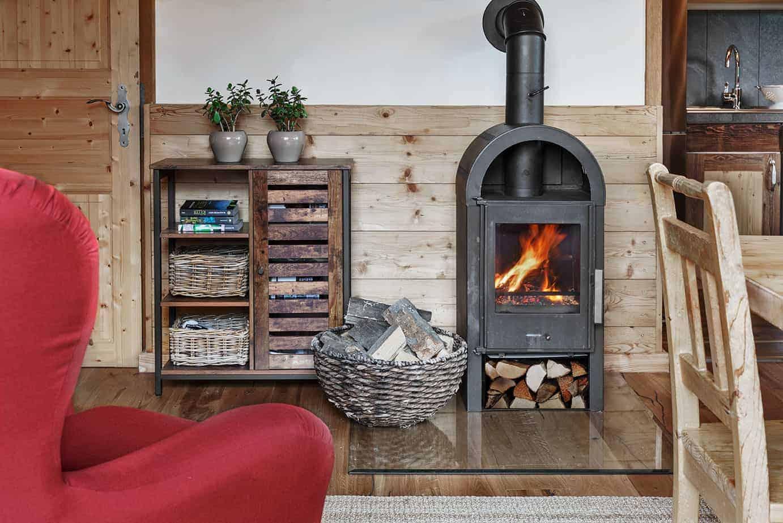 Ansicht eines kleinen Ofens mit Holzblöcken davor.