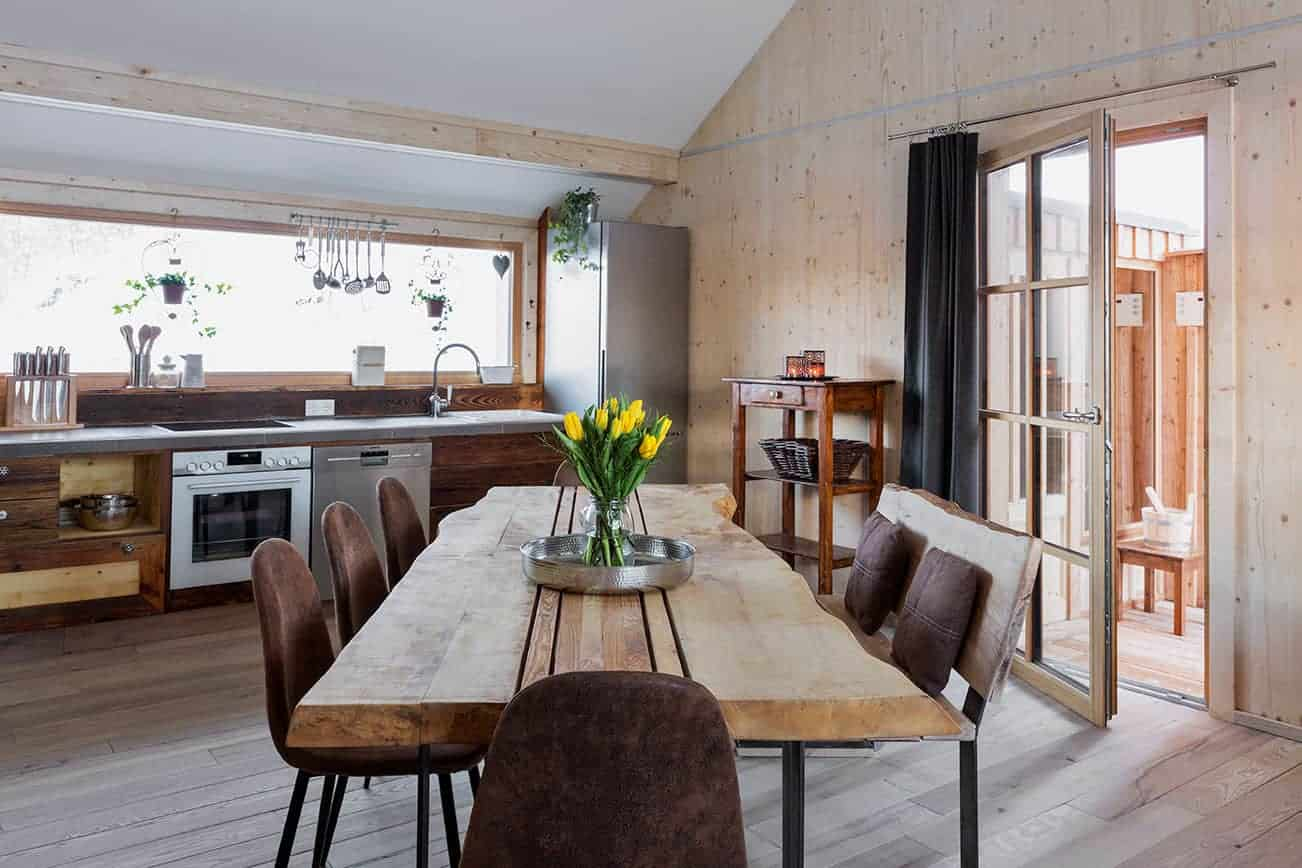 Bild einer Küche mit einem großen Tisch in der Mitte.