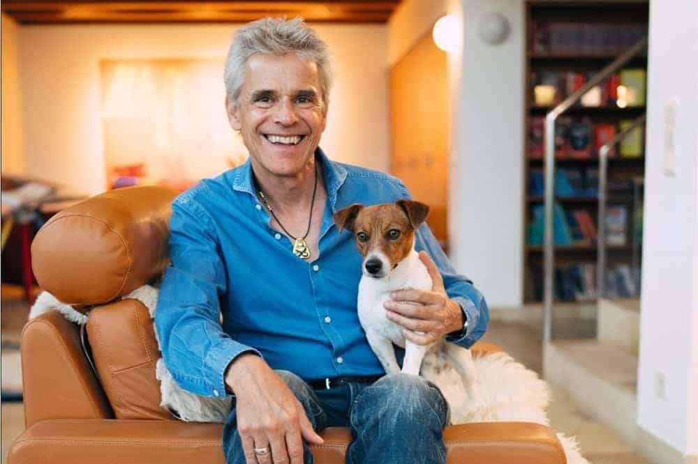 Thomas Brezina hat seinen Hund auf dem Schoß und sitzt auf einer braunen Ledercouch.