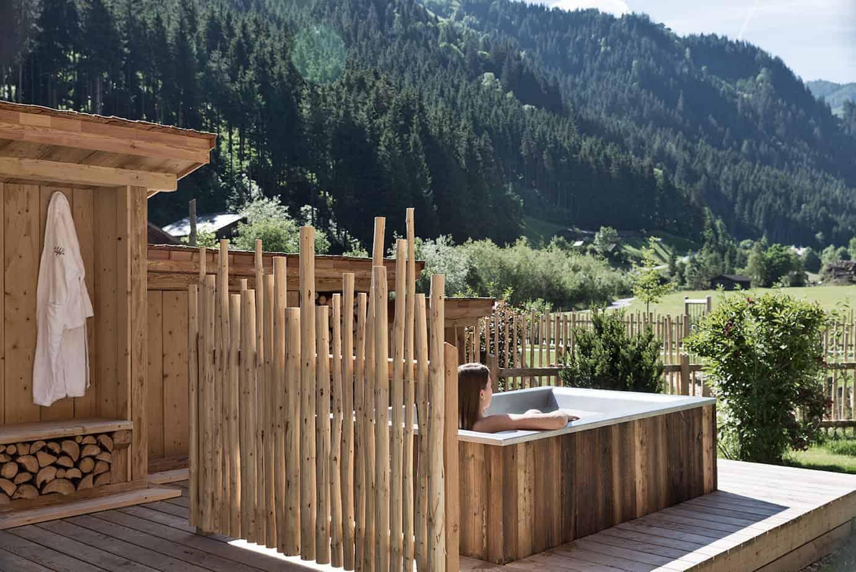 Am Foto sieht man eine im Freien stehende Badewanne mit Blick auf die Berge.
