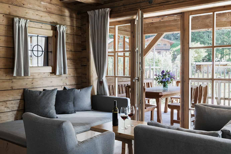 Innenaufnahme einer Hütte. Am Couchtisch stehen zwei Gläser und eine Flasche Wein.