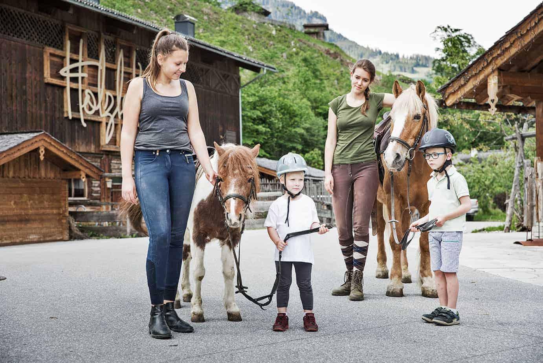 Am Foto sind zwei Ponies zu sehen, die von zwei Jungen Damen geführt werden und im Vordergrund sieht man zwei kleine Kinder mit Sturzhelmen stehen.